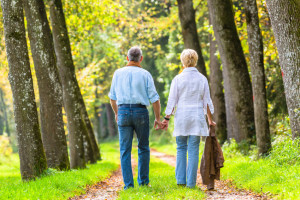 Couple of senior woman and man holding hands having a walk in autumn forest